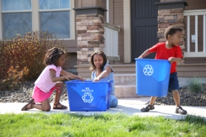 Children placing items in a Blue Box for recycling