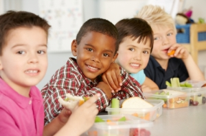 Group Of Elementary Age School Children Eating Healthy Packed Lunch In Class
