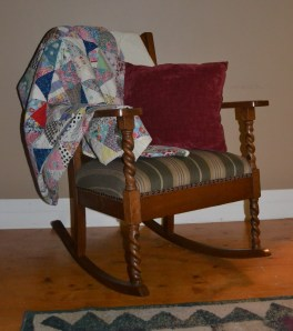 A rocking chair with a quilt draped over it