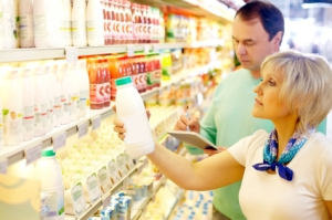 A woman and man check out an item from a grocery store shelf