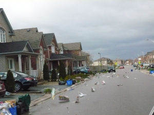 Newspaper blows down a residential street on a windy day