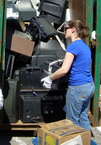 Laura lifting electronic waste in to a container at a Recycle Your Electonics event